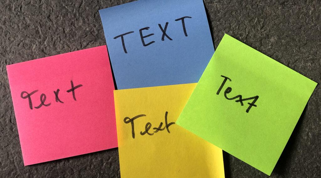 """Vier Post-its auf denen mit unterschiedlicher Handschrift das Wort """"Text"""" geschrieben steht. Text zur Seite Texte für Websites schreiben lassen"""